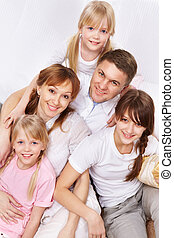 Parents and kids - A young friendly family sitting and...