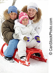 Children and mother - Happy kids sitting on sledge in park...