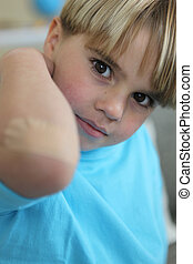 Little boy showing his bandage on elbow
