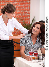 Waitress serving female customer
