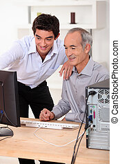 Younger and older men looking at a computer