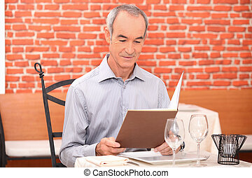 Man looking at a menu in a restaurant