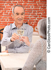 senior couple drinking champagne in a restaurant