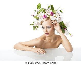 pretty blond with flower crown on head, looks in to the lens wit