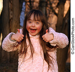 Portrait of beautiful happy girl giving thumbs up on...