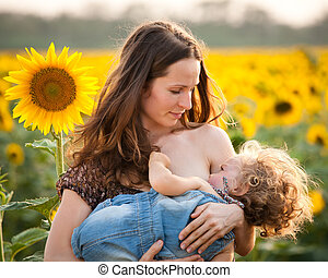 Woman breastfeeding baby - Happy woman breastfeeding baby in...
