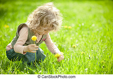 Beautiful child picks flowers on a spring green meadow