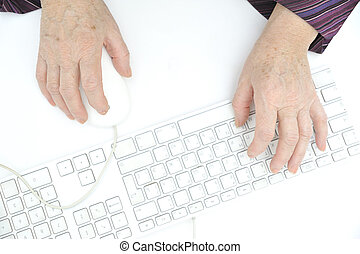 Hands of an old female typing on the keyboard and using...