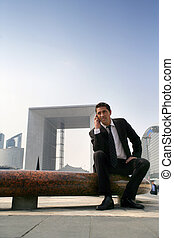 Man on phone sitting on a bench