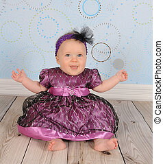 beautiful baby girl in dress sitting happily on floor