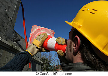 Laborer screaming in safety cone on construction site