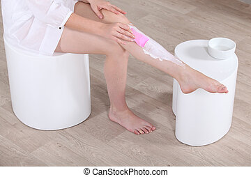 woman putting hair removal on her leg