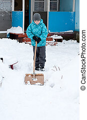 Boy removes snow around the House