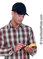 young electrician wearing cap using tester