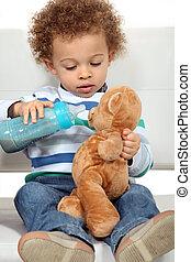 Little boy feeding teddy bear from bottle