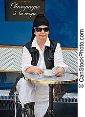 Coffee time - Young woman sitting in street cafe Paris