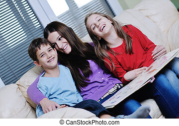 young mom play with their kids at home and reading book