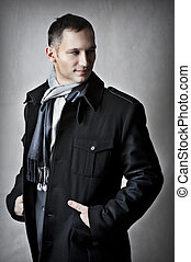 Fashion portrait of handsome young man model in black coat...