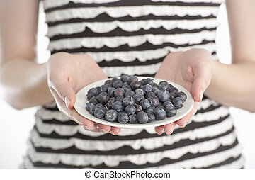 Young woman holding a plate with blueberries - Studio shot...