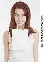 Young woman holding a white shopping bag in her mouth