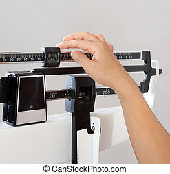 Woman on Weight Scale Closeup - Closeup view of womans hand...