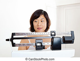 Woman Weighing on Weight Scale - Pretty woman closeup...