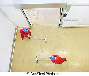 two workers cleaning floor - Overhead view of two workers in...