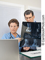 Doctor and Nurse Reading Spinal MRI Scan at the Computer -...