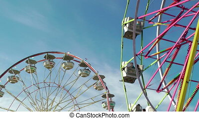 Ferris wheels at carnival against blue sky