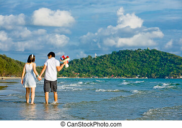 sweet couples walking by hand in hand along the beach with gentle ripple
