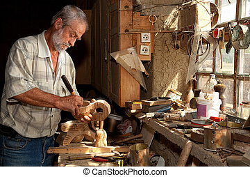 Wood worker in old shed - Wood worker carving wood in a...