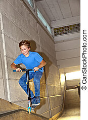 boy jumping with his scooter over a ramp in the skatehall