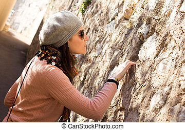 Woman Looking Into A Hole In A Stone Wall - Interested Woman...