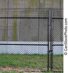 A chain link fence lined with barbed wire along the top and...