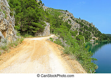 Dirt road by lake - Dirt road by the lake at sunny day
