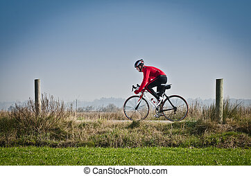 Cyclist - Man on road bike riding down open country road