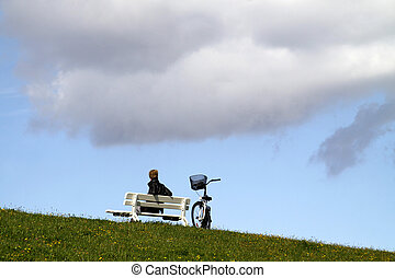 Woman sitting on a bench on a North Sea dike, next to a bicycle