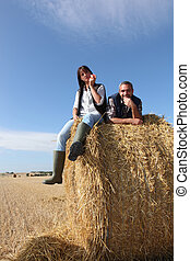 Couple sitting on bail of hay