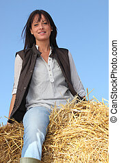 Woman sitting on bale of hay