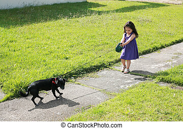 Little girl having trouble with her dog in the park