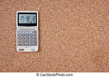 electronic calculator on a cork board