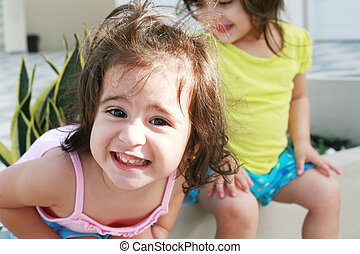 Sweet little girls in front of her little house for playtime (focus on the front girl)