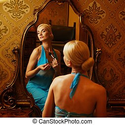 Woman in blue dress reflected in mirror