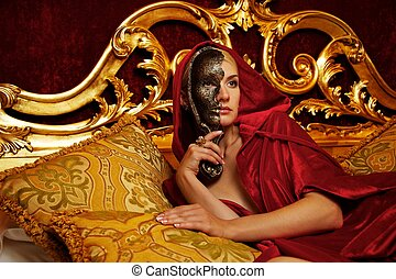 Beautiful woman with a carnival mask lying on bed