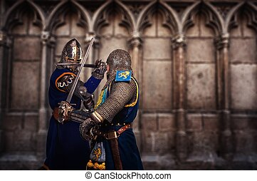 Two knights fighting against medieval cathedral wall.