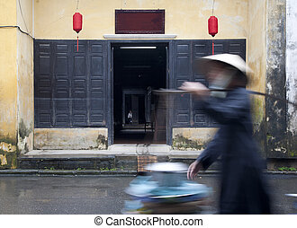 Hoi An street scene - Street vendor walking past a...