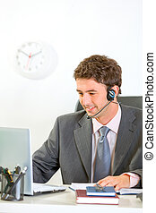 Smiling modern businessman with headset looking in laptop