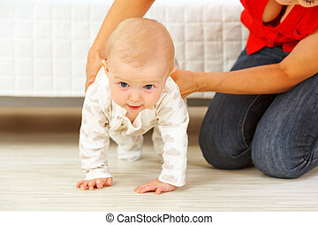 Mother helping cheerful baby learn to creep