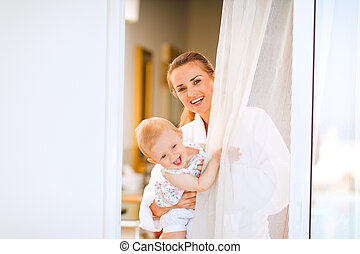 Portrait of smiling mother in bathrobe with baby looking out from window