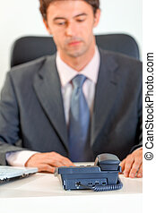 Modern businessman sitting at office desk and expecting...